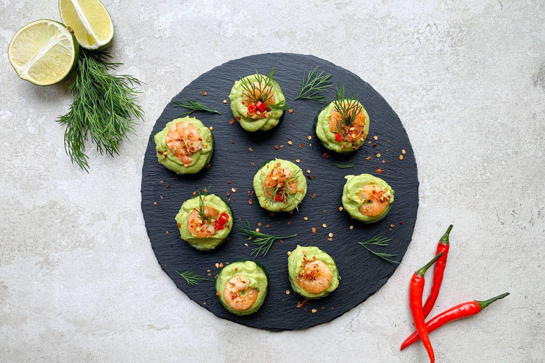 Garnelen-Avocado-Türmchen mit frischem Dill garniert auf einem runden Schieferteller angerichtet, daneben halbierte Limetten und frische Chilischoten