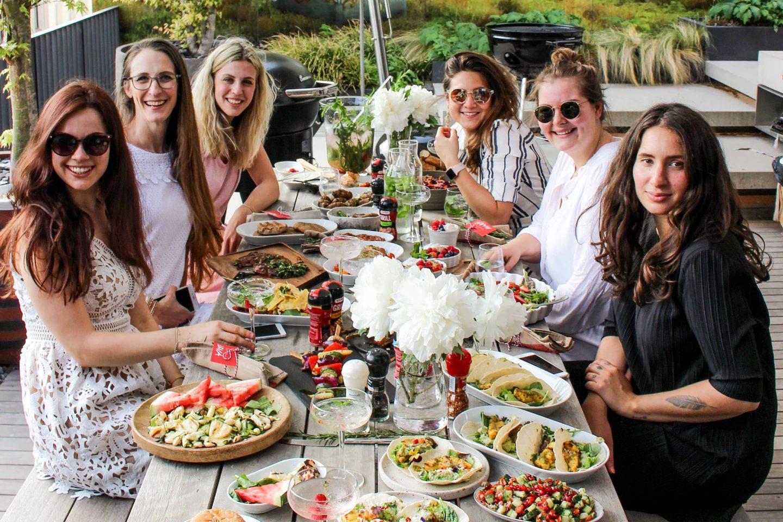 an einem Tisch sitzende Foodblogger mit ihren Gerichten