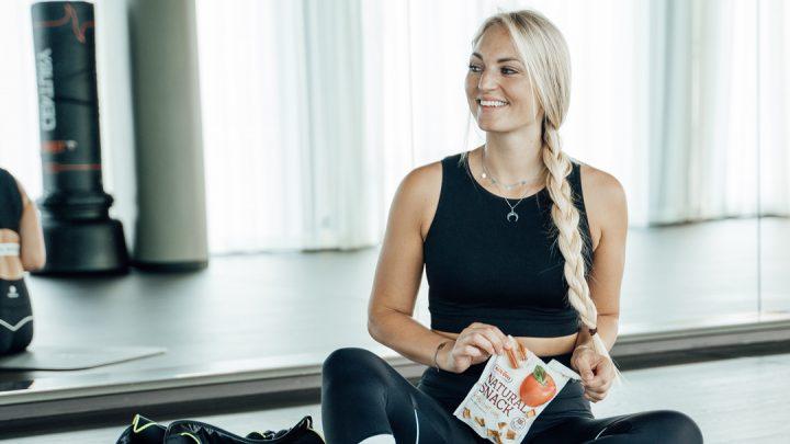 Bloggerin Carina Berry mit Natural Snack Apfel Zimt beim Fitnesstraining
