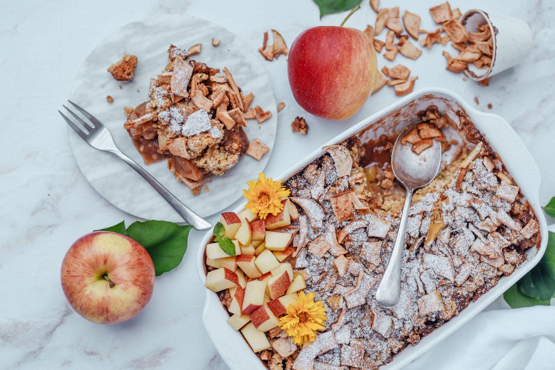 Apfel-Crumble mit Apfel-Zimt- Chips in einer Auflaufform und Äpfeln