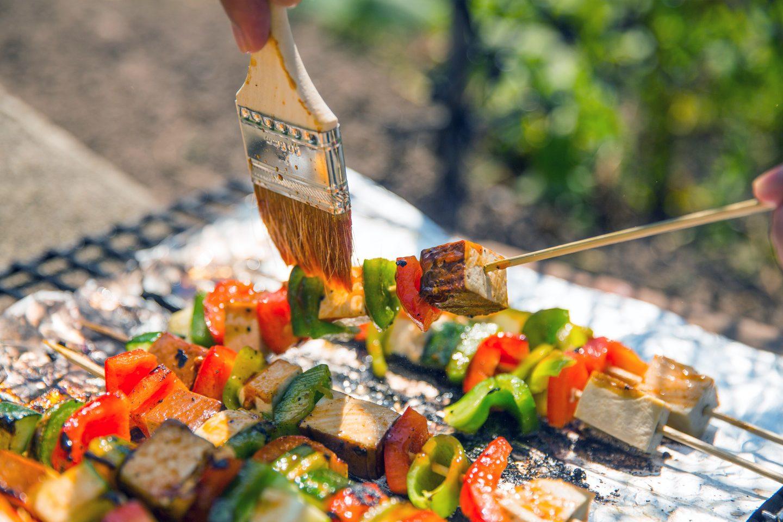 Tofu-/ Gemüsespieße werden mit einem Pinsel mariniert