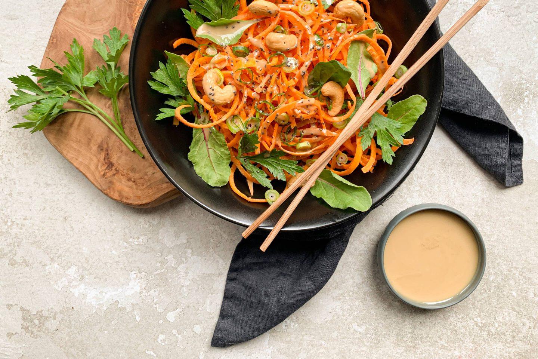 Frische, rohe Karotten-Spaghetti mit würziger Tahinsauce in einem schwarzen, tiefen Teller