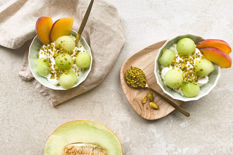 fruchtiges Joghurt mit Melone, Pfirsich und Pistazien garniert