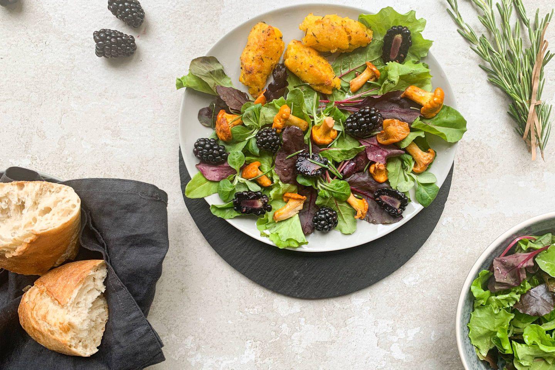 Eierschwammerl Salat mit Brombeeren und Brot auf einem hellgrauen Teller angerichtet