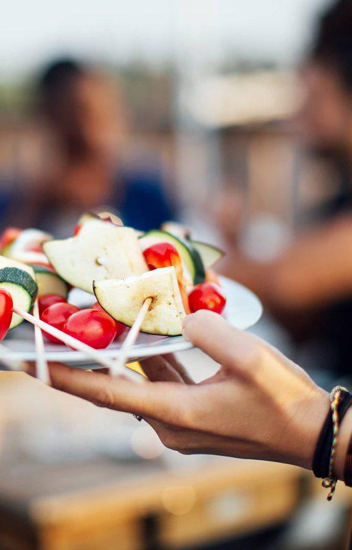 Frauenhand hält Teller mit veganen Grillspießen