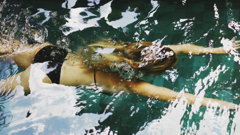 Frau schwimmt in klarem Wasser