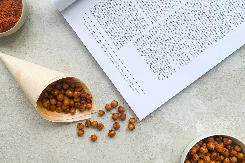 Gebackene Kichererbsen mit Cayennepfeffer in einer Schüssel und in einem Tütchen neben einem Magazin