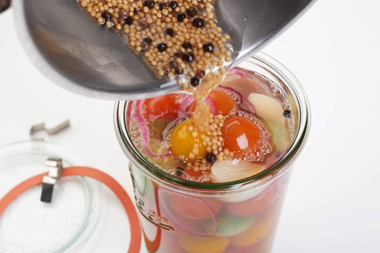 Eingelegte Cherry-Tomaten in einem Rexglas werden gerade mit Sud übergossen