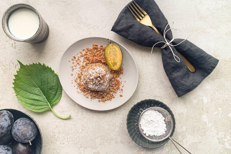 Zwetschkenknödel in Haselnusskrokant-Mantel auf einem grauen Teller mit Staubzucker, frischen Zwetschken, goldenem Besteck und grauer Serviette
