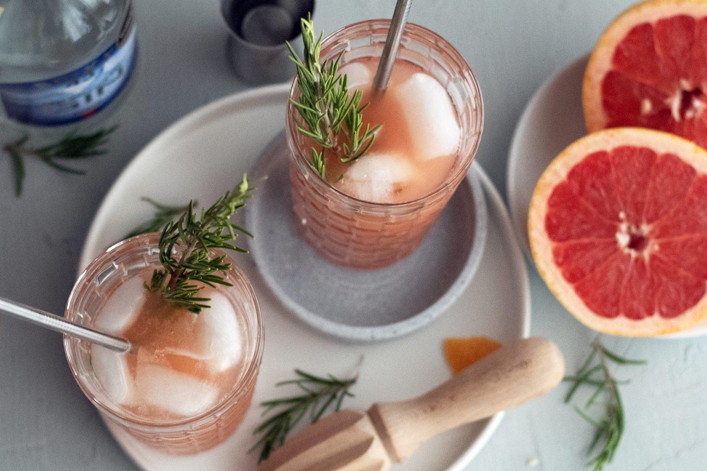 Gin Getränk im Glas mit Rosmarinzweig, Grapefruit und Strohhalm
