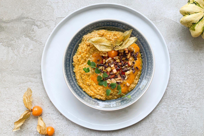 Goldenes Kürbis Porridge auf einem Teller angerichtet mit Physalis verziert
