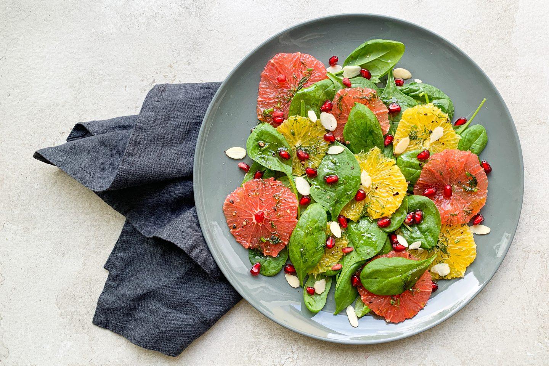 Orangen-Spinat Salat auf einem Teller angerichtet mit Granatapfelkernen garniert