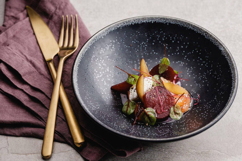 Lauwarme Rote Rüben mit karamellisierten Zwetschken und Ziegenfrischkäse in einem schwarzen tiefen Teller mit goldenem Besteck