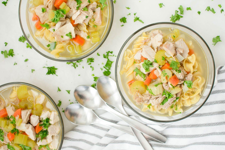 3 Teller mit Hühnersuppe mit Karotten, Nudeln und Sellerie