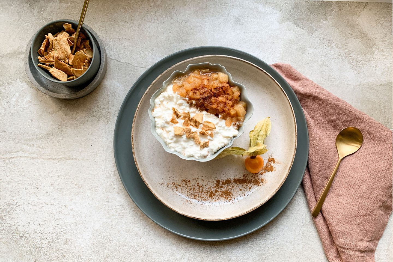 Hüttenkäse mit Apfel und crunchy Topping in einer Schale auf einem Teller mit Physalis angerichtet