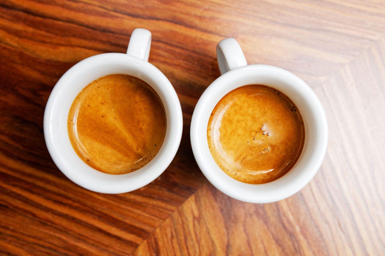 2 Tassen mit Espresso und Crema auf einem Holz-Untergrund