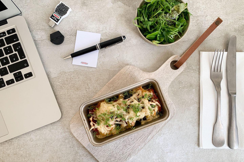 Erdaepfel Auflauf in einer kleinen Kastenform am mobilen Arbeitsplatz mit Laptop