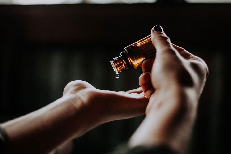 Frauenhand gießt ätherisches Öl in die andere Handfläche
