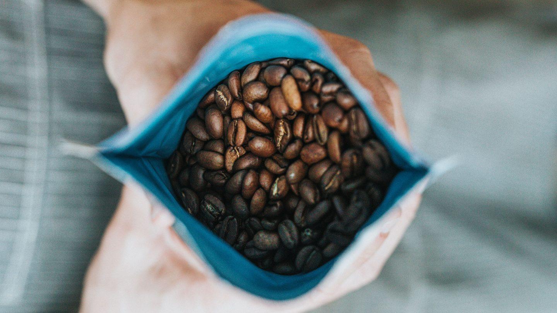 2 Hände halten einen Beutel mit frischen Kaffeebohnen