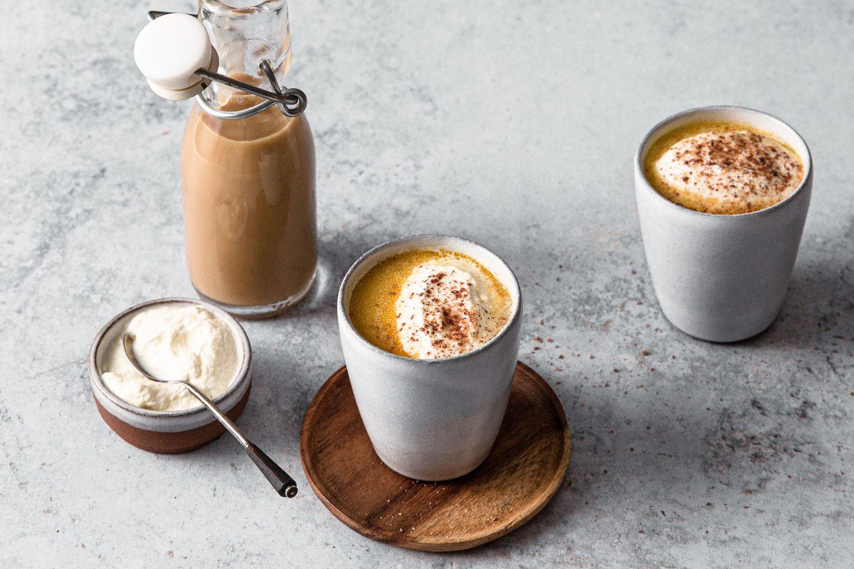 2 Becher mit Chai Coffee Eierlikoer die auf Holztellerchen stehen, eine kleine Schale mit Schlagobers und Löffelchen und eine Flasche mit dem Eierlikör im Hintergrund. Alles steht auf einer grauen Platte.
