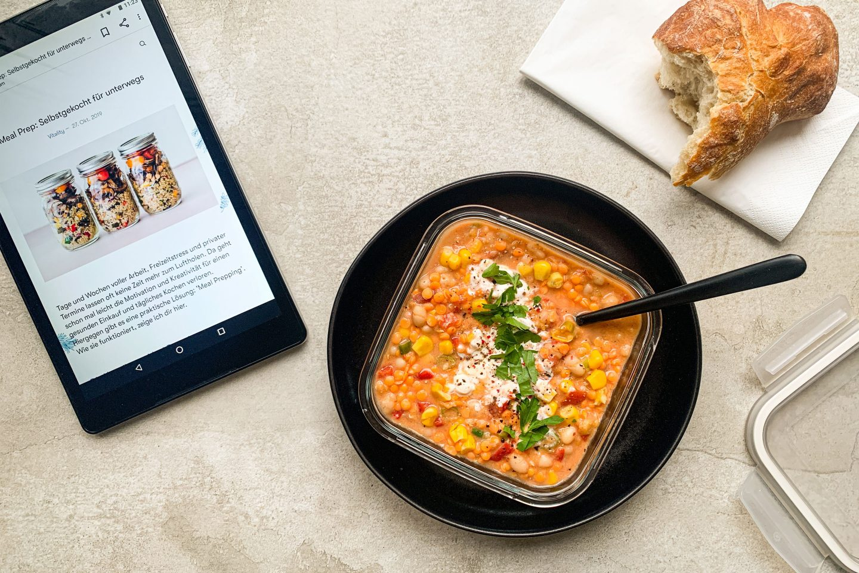 Feuriges Rote Linsen Chili mit Mais, weißen Bohnen und Sauerrahm in einer Mealprep-Form für unterwegs zubereitet