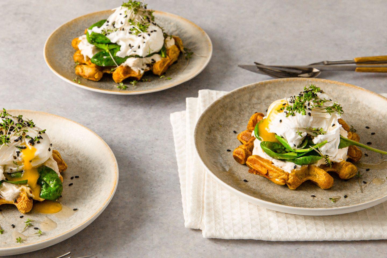 Suesskartoffelwaffel Mit Topfen und pochiertem Ei übereinander getürmt auf 3 Tellern angerichtet und Kräutern bestreut