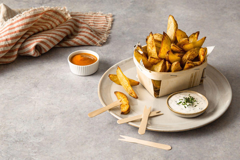 Crunchy Potato Wedges Mit Dips in einem Holzkörbchen auf einem Teller serviert