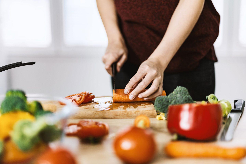 eine Frau mit dunkelroter Schürze schneidet Karotten, Tomaten und anderes Gemüse auf einem Brett