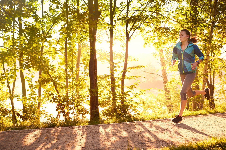 eine Frau beim Joggen durch einen Licht durchfluteten Laubwald