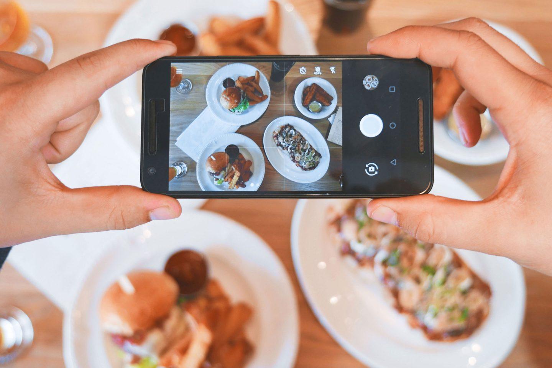 Männerhände halten ein Smartphone mit dem Fokus auf einen Tisch mit Essen gerichtet