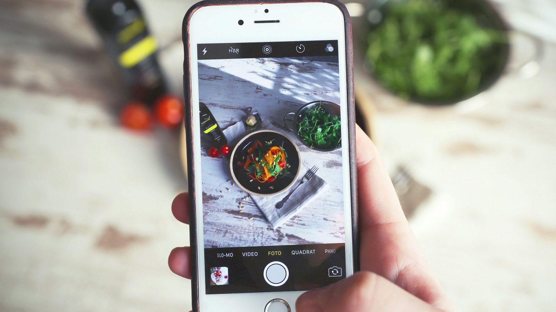 eine Hand hält ein Smartphone das gerade eine Holzplatte mit einem Teller voll frischem Salat fokussiert