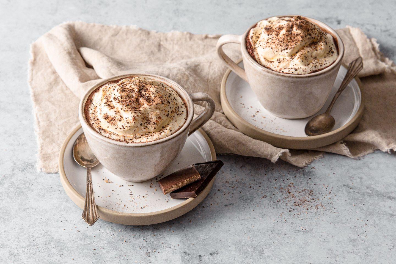 2 Tassen mit heißer Schokolade und Schlagoberhäubchen mit Cacao Kiss Topping aus der Mühle, mit Schokostückchen auf der Untertasse angerichtet