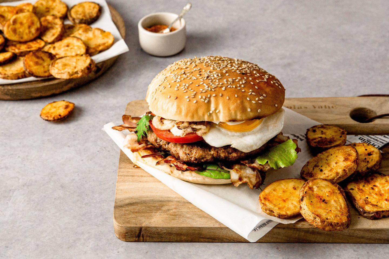 Spicy Potatoes Mit Western Burger mit Ei auf einem Brett angerichtet