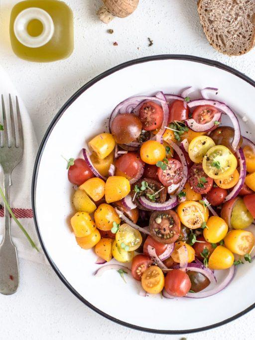 Salat aus halbierten gelben und roten Cocktailtomaten in einem tiefen weißen Teller auf weißem Untergrund