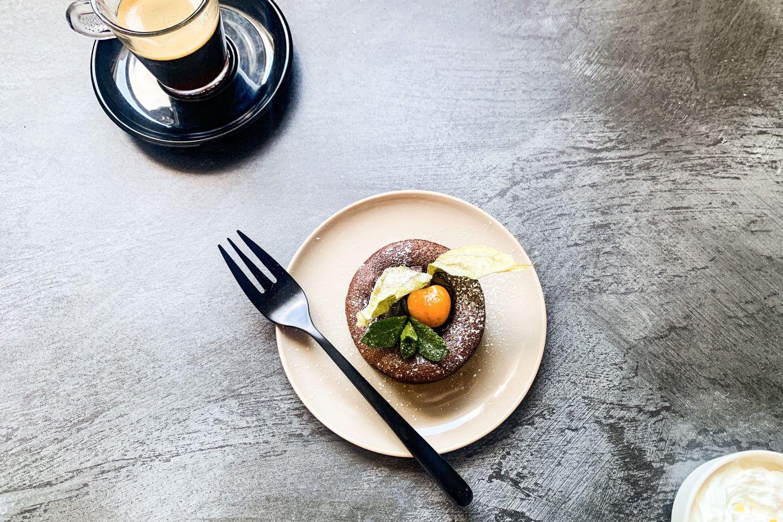Spicey Schoko-Lava-Cake mit einer Physalis garniert auf einem hellen Teller