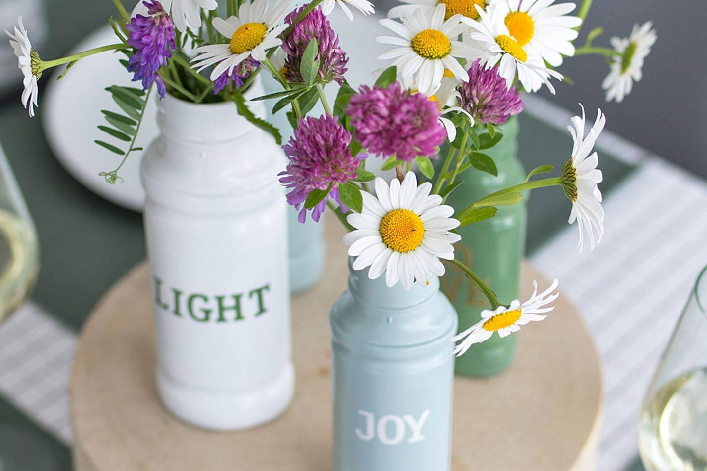 die fertigen DIY-Gewürzglas-Vasen mit frischen Wiesenblumen