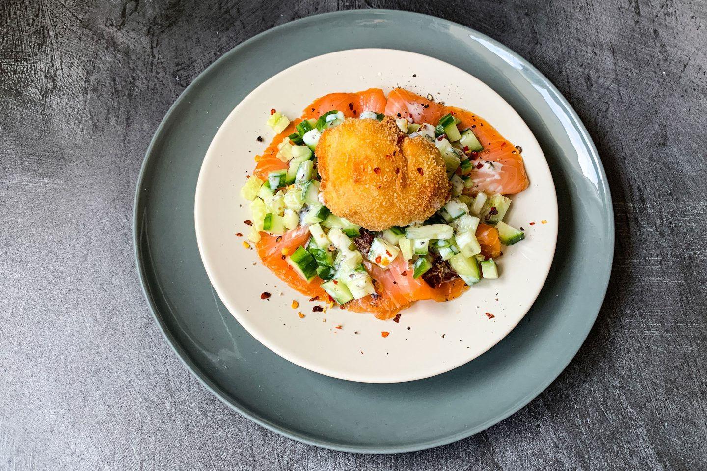 Dattel-Gurken-Salat mit Lachs und einem gebackenem Ei auf einem hellen Teller und einem grauen Platzteller