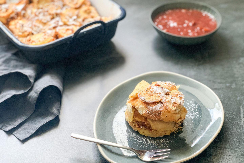 Teller mit einem Stück Osterpinze-Scheiterhaufen und Gabel, im Hintergrund die Ofenform mit dem REts und Kompott in einer Schüssel