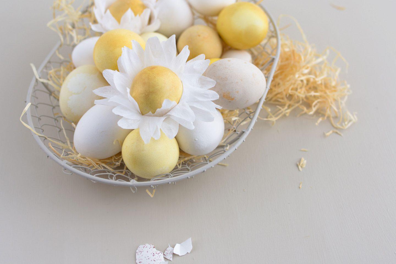 gefaerbte Eier in einem Körbchen, 2 mit selbstgebastelter Blüte aus Krepp-Papier