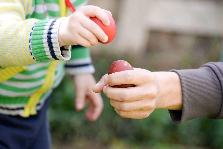 Kinder- und Erwachsenenhand haben ein Ei und klopfen es gegeneinander