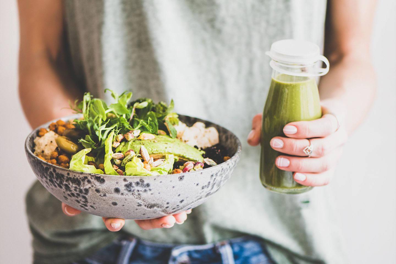 Eine Frau hält eine Bowl mit Gemüse und Reis und einen grünen Smoothie in beiden Händen