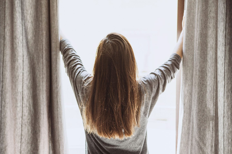 Eine Frau zeiht die Vorhänge vor einem Fenster auf