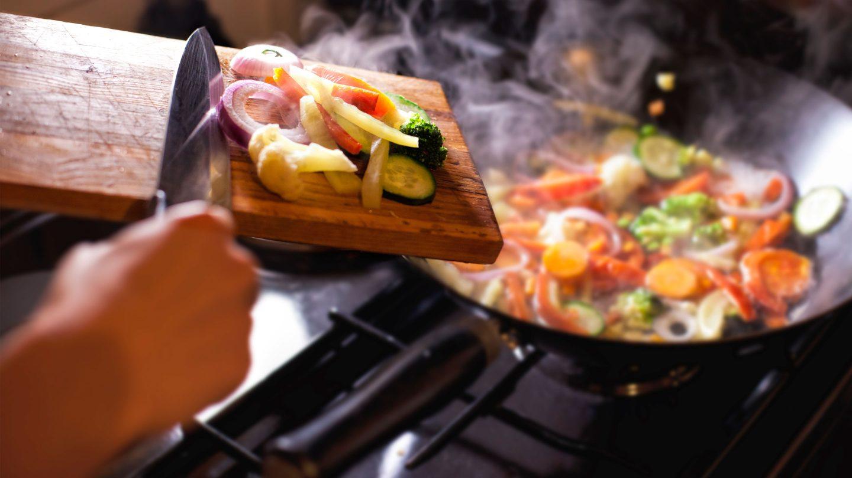 geschnittenes Gemüse wird mit einem Messer von einem Brett in den Wok geschoben