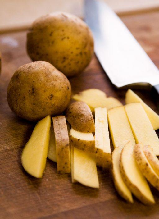 in Stifte geschnittene Kartoffeln mit einem Messer auf einem Brett