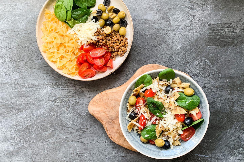 ein tiefer Teller mit One-Pot-Farfalle zubereitet aus Tomatenspalten, Oliven und Babyspinat, ein weiterer Teller mit den Zutaten