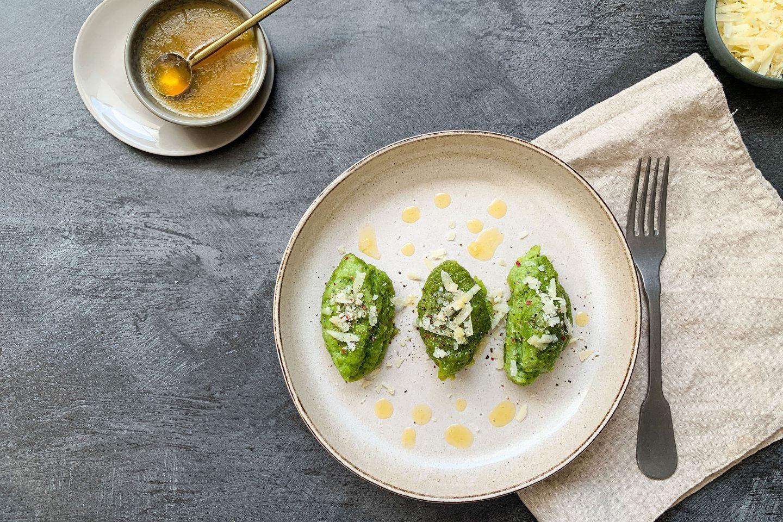 3 Bärlauch-Nockerl auf einem Teller mit Butter beträufelt und Parmesan bestreut