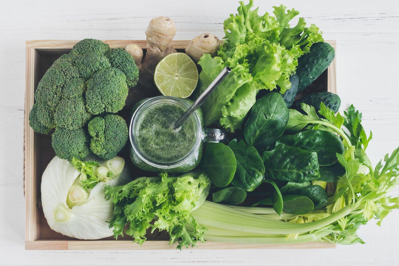 Eine Holzkiste voller grüner Gemüse- und Obstsorten zum Smoothie mixen