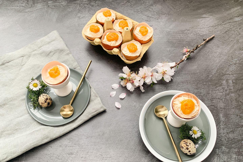 Süße, halbe Eier im Eierbecher und im Eierkarton arrangiert