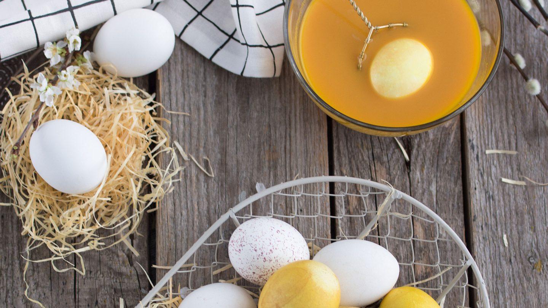 mit Curcuma gefärbte Eier in einem Korb und ein Ei im Färbebad
