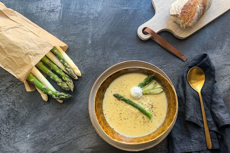 Spargelcreme-Suppe mit grünem Spargel in einem tiefen Teller; daneben liegt ein Stück Baguette und Spargel